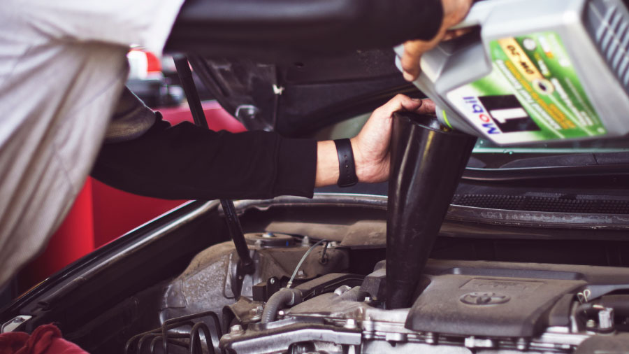 Mechanic filling a car with motor oil.