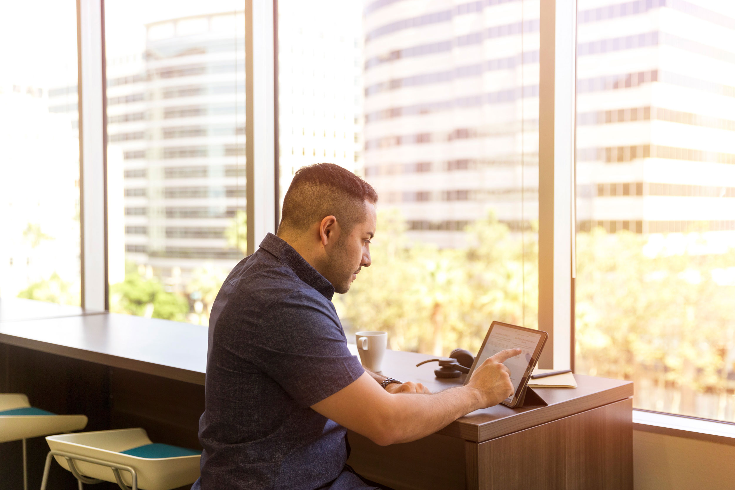 Man near window viewing and touching a digital tablet