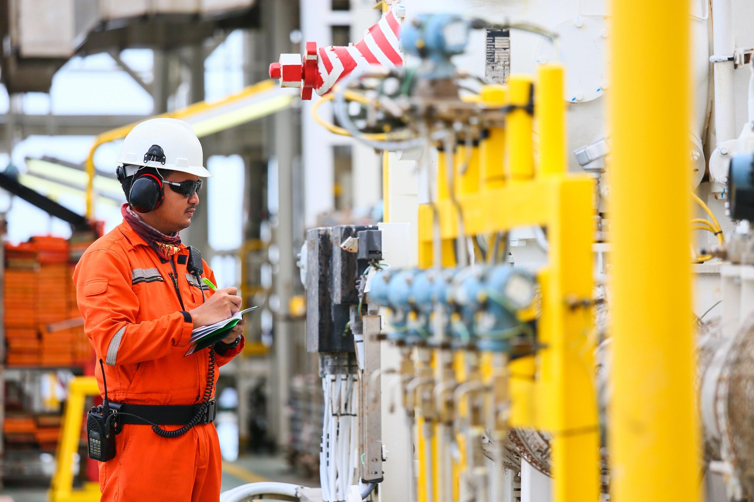 man in industrial environment monitoring equipment