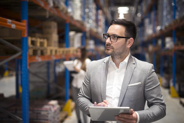 Man wearing a suit and glasses on warehouse floor holding a tablet.