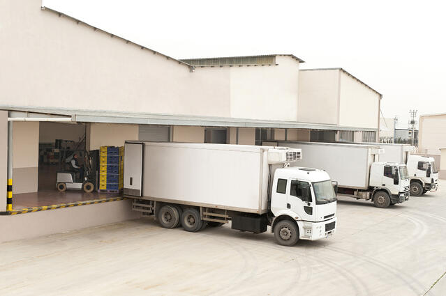 The back of a white warehouse with three large delivery trucks.