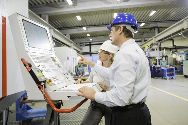 Man and women wearing white and blue hard hats in a warehouse looking at a machine screen.