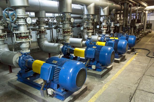 four blue and yellow industrial machines in a warehouse