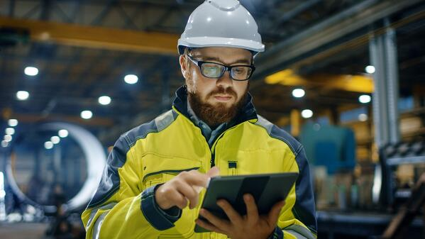 Manufacturing operations plant manager reviews IoT application data on iPad