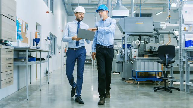 Middle aged man and a younger man wearing hard hats in a manufacturing warehouse talking and holding a laptop.