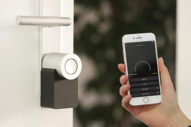 """Iphone with a """"Smart Locks"""" Application in a hand. Next to a Smart lock on a white door."""