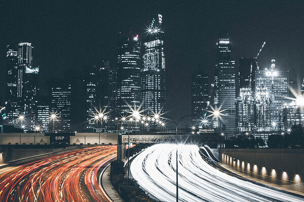 City skyline at night with a car headlight hyperlapse to indicate high speed.